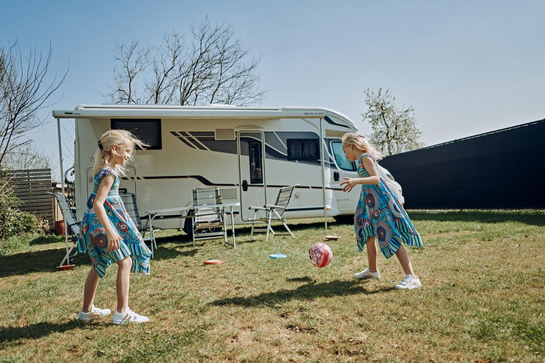 De tweelingzusjes Anouk en Alyssa Van Vosselen voetballen in de tuin. Soms slapen ze met papa in de mobilhome 'voor het vakantiegevoel'. Beeld Thomas Sweertvaegher