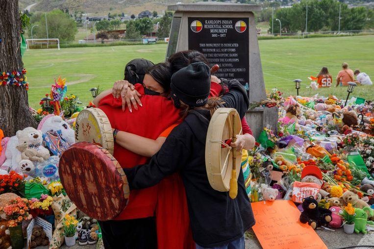 Mensen knuffelen bij een geïmproviseerd herdenkingsmonument. Beeld AFP