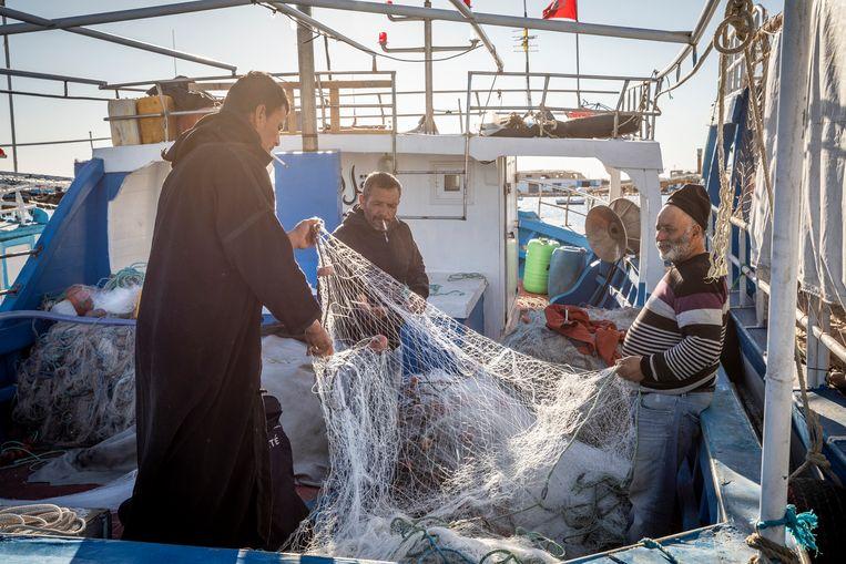 Vissers in de haven van Zarzis. Sinds 2018 zijn zij medeplichtig aan mensensmokkel wanneer ze drenkelingen redden op zee. Beeld Sven Torfinn / de Volkskrant