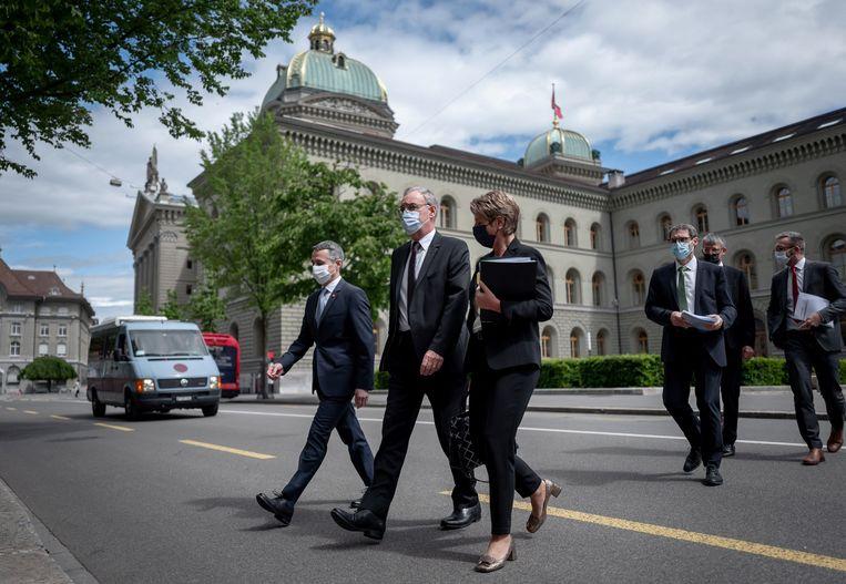 De Zwitserse buitenlandminister Cassis, president Parmelin en justitieminister Keller-Sutter komen aan bij een persconferentie, waar zij zouden aankondigen geen handelsakkoord met de EU te willen sluiten. Beeld AFP