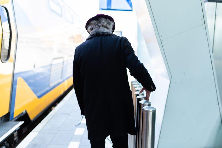 Een blinde zoekt zijn weg op een station.  Beeld Katja Poelwijk