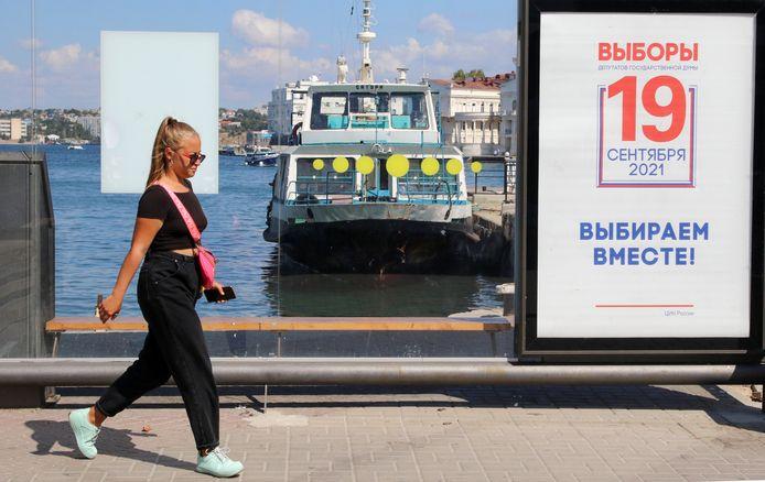 Une femme passe devant un arrêt de transport public et une affiche informant des prochaines élections parlementaires russes à Sébastopol, en Crimée.