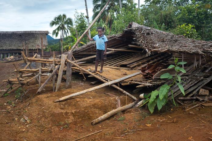 Een 10-jarig jongetje voor zijn ingestorte huis in Papoea-Nieuw-Guinea, na de aardbeving  van eind februari.