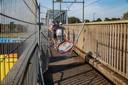 Een groepje jongeren wurmt zich tussen de hekken door nadat ze op de landtong van de zon hebben genoten.