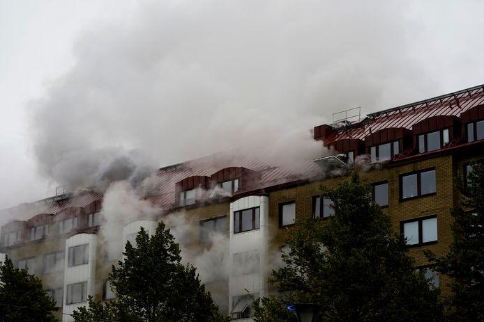 Er komen nog steeds dikke rookpluimen uit het dak van het gebouw.