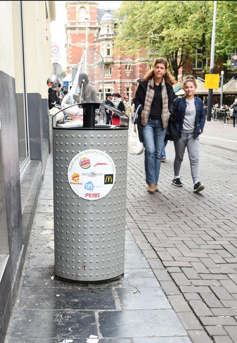 Een vuilnisbak in de Leidsestraat met logo's van winkels en restaurants Beeld -