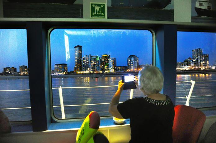 De bezoekers aan de 'Drijf-uit', de filmvoorstelling op de Westerschelde Ferry, hadden soms meer oog voor het uitzicht dan voor de film. In het raam is de weerspiegeling van het filmdoek te zien.