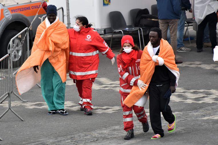 Vluchtelingen die gered werden door de Italiaanse kustwacht komen aan land in havenstad Catania. Beeld AFP