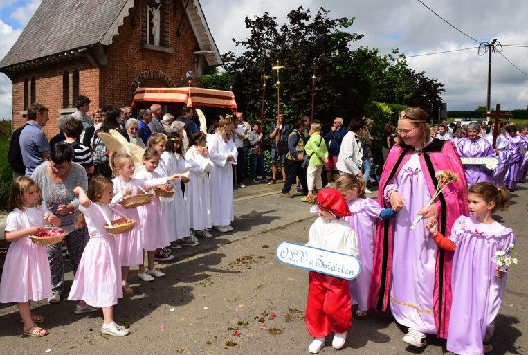 Enkele meisjes gooien bloemblaadjes als de processie  langskomt.