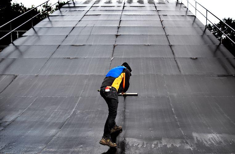 Sander Bisseling, de ontwerper en mede-bouwer van de BMX-baan, veegt het regenwater van de startheuvel. Het startgedeelte op Papendal is een kopie van de olympische baan in Tokio. De Zomerspelen beginnen over 284 dagen. Beeld Klaas Jan van der Weij