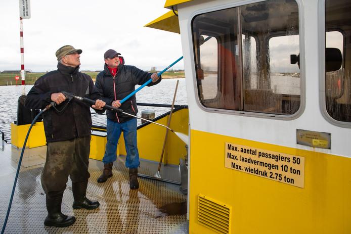 Gijs Hartog en Evert Hoolwerf (groene pet) waren vanochtend druk op het pont over de Eem met de schoonmaak.