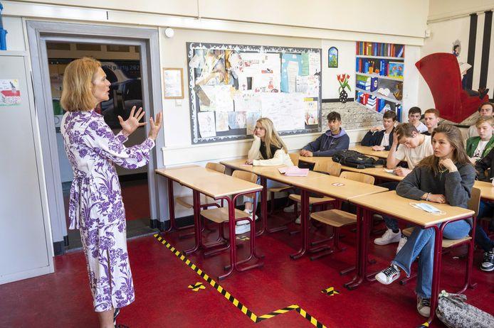 Een lerares geeft les in een geventileerd klaslokaal.