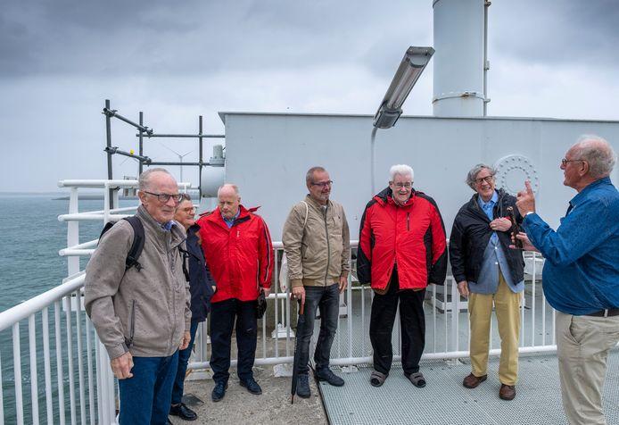 Gids Tjibbe de Vries (rechts) praat de Limburgers bij over de Oosterscheldekering. In het midden Ludie Thijssen (met paraplu) van KBO Valkenburg.