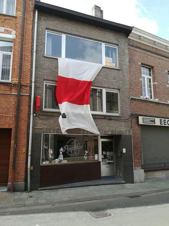 Joost Dierickx had niet meteen een vlag bij de hand en versierde de gevel van zijn café In De Poepekas dan maar met een gigantische wimpel van de vendeliers van volkskunstgroep Reynout.