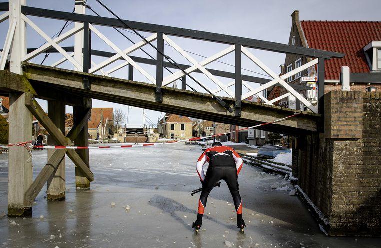 Henk Angenent negeert een waarschuwingslint en schaatst onder een bruggetje door in Hindeloopen. Slecht ijs dwingt hem twee steden te schrappen Beeld ANP