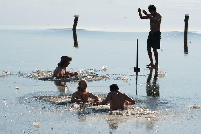 Mannen hakken in de uiterwaarden bij Wageningen ijs weg. In het wak gaan ze rustig zitten schaken.
