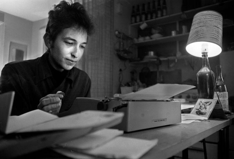 Bob Dylan schrijvend aan zijn bureau in 1964.  Beeld ANP