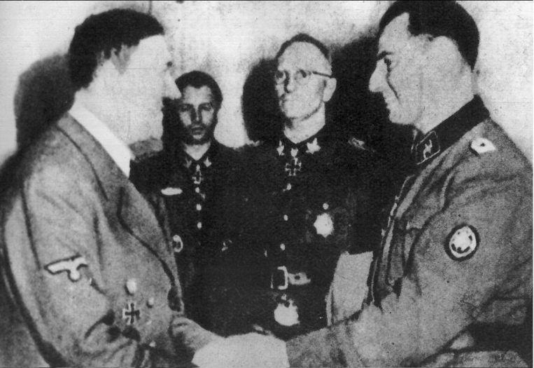 Hauptsturmführer Degrelle in 1944 op audiëntie bij Hitler na de slag bij Tsjerkasy (Oekraïne).De Führer beloont hem met het prestigieuze Ridderkruis met Eikenloof.    Beeld BELGAIMAGE