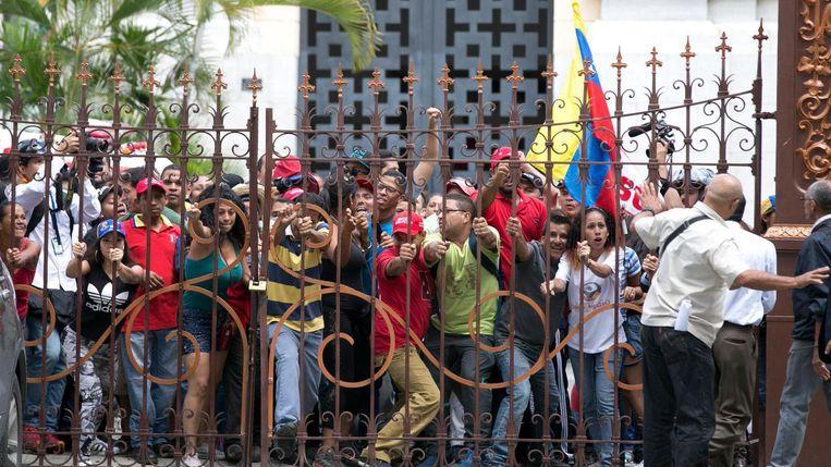 Aanhangers van president Maduro proberen het regeringsgebouw binnen te komen Beeld AP