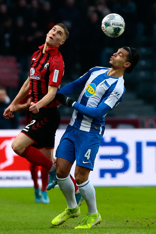 Karim Rekik (r) vecht een luchtduel uit met Roland Sallai van Freiburg.