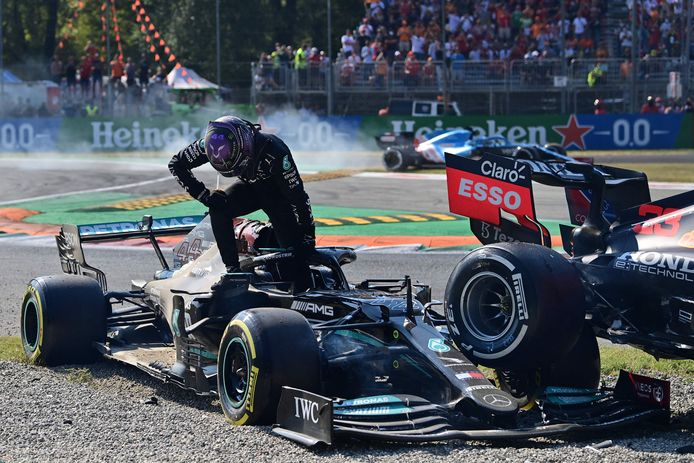 Hamilton kruipt uit zijn wagen, terwijl die van Verstappen er bovenop staat.