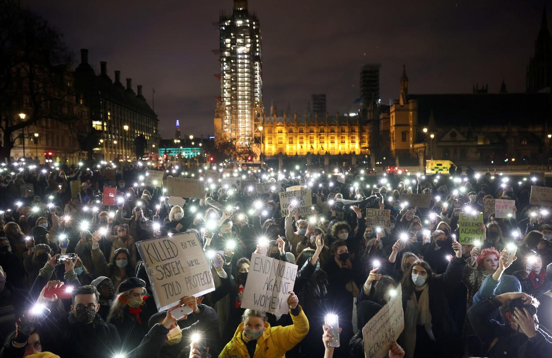 Londenaren zetten bij Parliament Square de zaklampjes aan van hun mobiele telefoons bij een wake voor de vermoorde Sarah Everard.  Beeld Henry Nicholls / Reuters