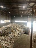 Een vrachtwagen rijdt de loods binnen en loost het plastic afval