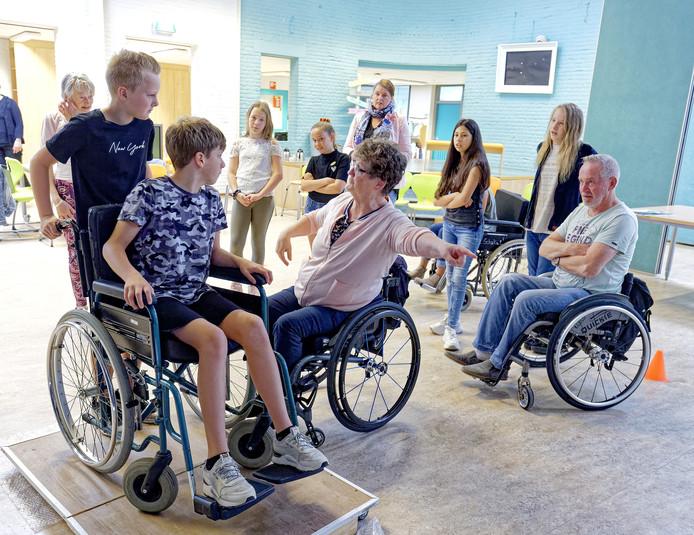 Leerlingen van basisschool 't Kwekkeveld in Schijndel krijgen info van de stichting Toegankelijkheid Meierijstad over het gebruik van een rolstoel.