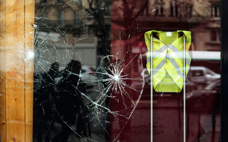 Een vernielde etalage met daarin een geel hesje, een steunbetuiging aan de demonstranten, 2 december in Parijs. Beeld AP
