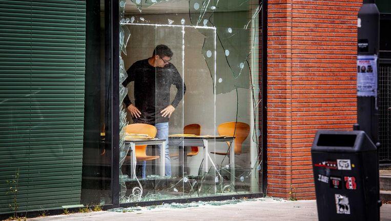 Een medewerker van Pijper Media, uitgever van onder andere Panorama, bekijkt de schade die is ontstaan door de beschieting met een antitankwapen Beeld ANP