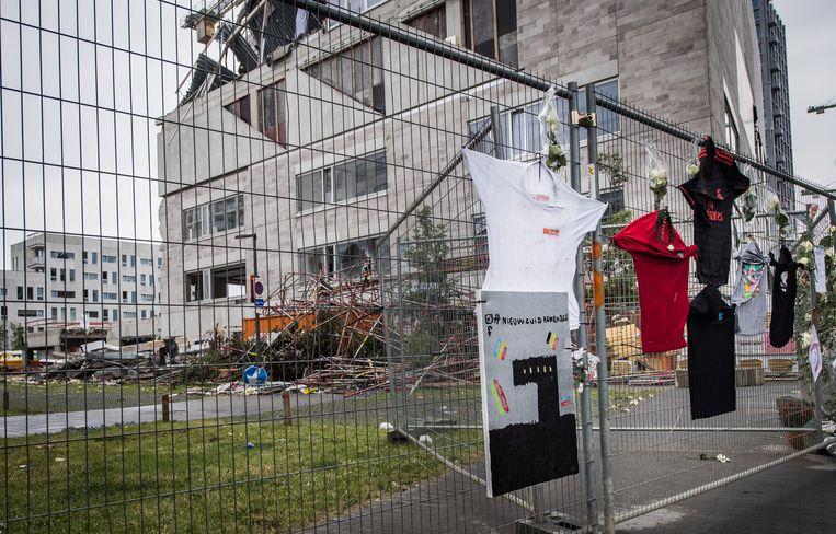 Aan de ingestorte school hangen bloemen, tekeningen en T-shirts om de vijf omgekomen arbeiders te herdenken. Beeld Joel Hoylaerts / Photo News