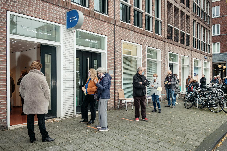 Een lange rij griepprikgegadigden voor gezondheidscentrum De Keyzer. Beeld Jakob van Vliet