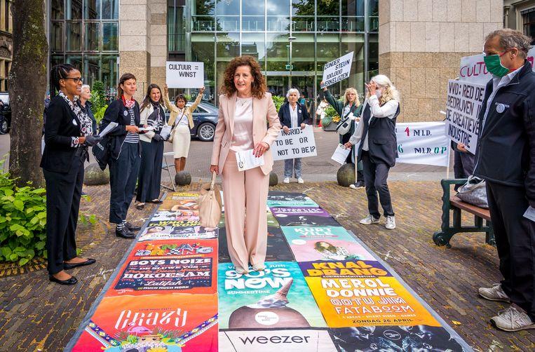Minister Ingrid van Engelshoven (Onderwijs, Cultuur en Wetenschap) loopt over een loper gemaakt van posters van geannuleerde voorstellingen en concerten.  Beeld Hollandse Hoogte / ANP