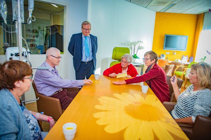 Vrijwilligers Marian Vink (rechts in het rood) en Cilly Stok (uiterst rechts) met een paar patiënten aan de tovertafel. Hilbrand Nawijn is blij met de aanschaf van het interactieve spel.
