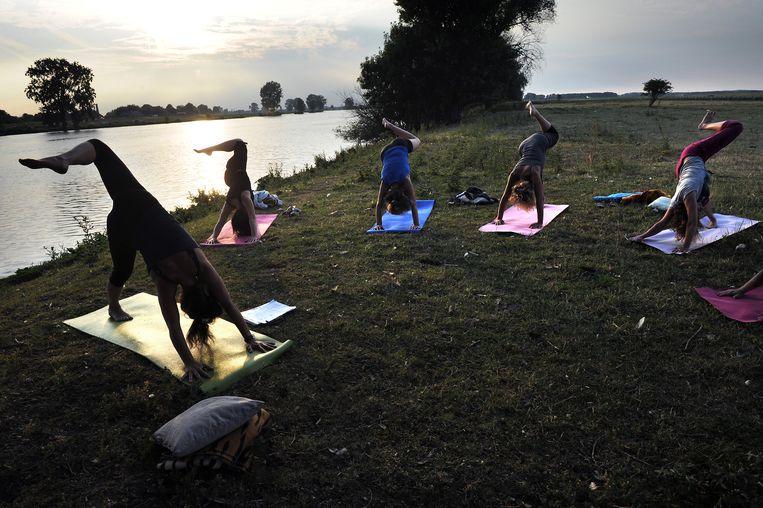 Yoga langs de Maas. Beeld Marcel van den Bergh