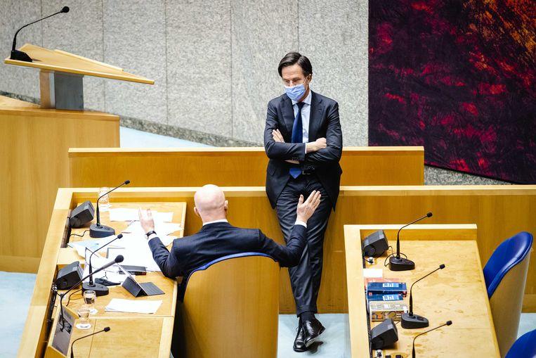 Ferdinand Grapperhaus, demissionair minister van Justitie en Veiligheid, en demissionair premier Mark Rutte tijdens een schorsing van het debat in de Tweede Kamer over de nieuwe spoedwet over de avondklok.  Beeld ANP