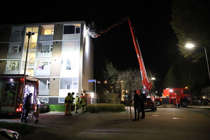 Vanuit de hoogwerker van de brandweer vindt inspectie van de buitengevel van de flat in Tiel plaats nadat bewoners een grote barst in hun binnenmuur hebben ontdekt.