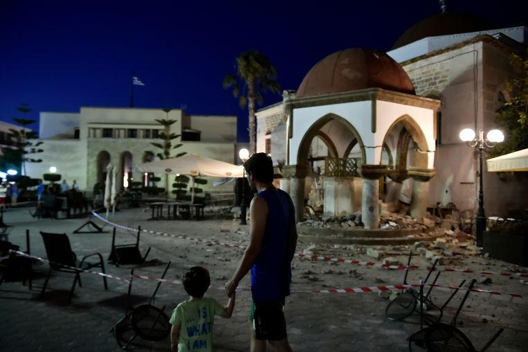 Peope walk next to a damaged building in central Kos, following a 6.7 magnitude earthquake which struck the region, on July 21, 2017. A 6.7-magnitude undersea quake hit the Greek holiday island of Kos and the Turkish resort of Bodrum on July 21, killing two people and injuring hundreds in areas abuzz with nightlife. The epicentre of the quake was about 10 kilometres (six miles) south of Bodrum, a magnet for holidaymakers, and 16 kilometres east of Kos, the US Geological Survey said. / AFP PHOTO / LOUISA GOULIAMAKI Beeld AFP