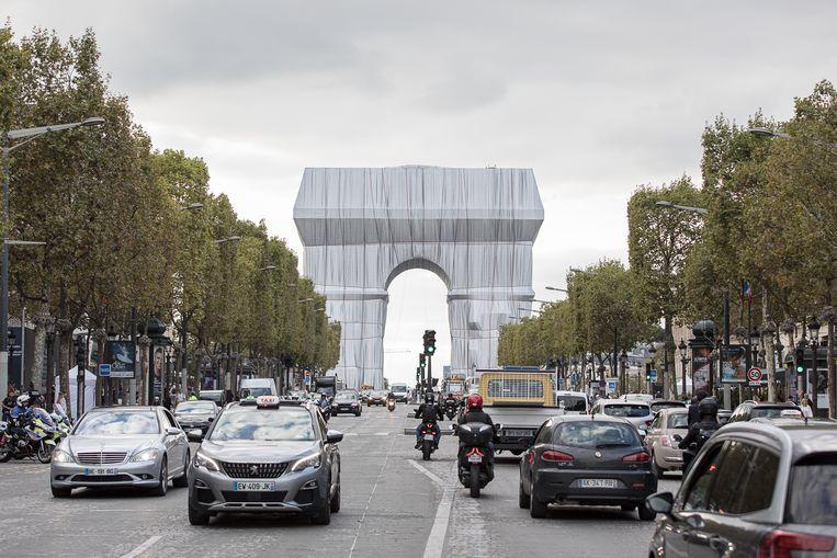 De ingepakte boog doemt op aan het einde van Champs-Élysées.  Beeld Natascha Libbert