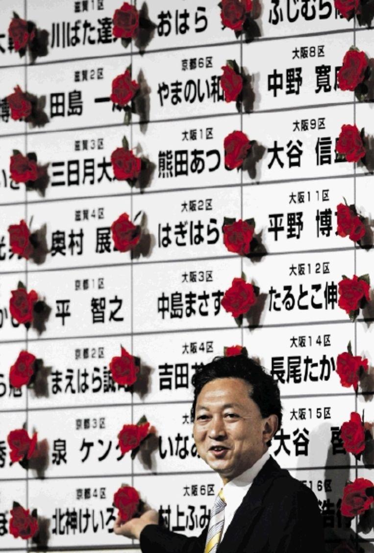 De nieuwe Japanse leider Hatoyama bij rozetten die de winst van zijn kandidaten aangeven. (FOTO REUTERS) Beeld REUTERS