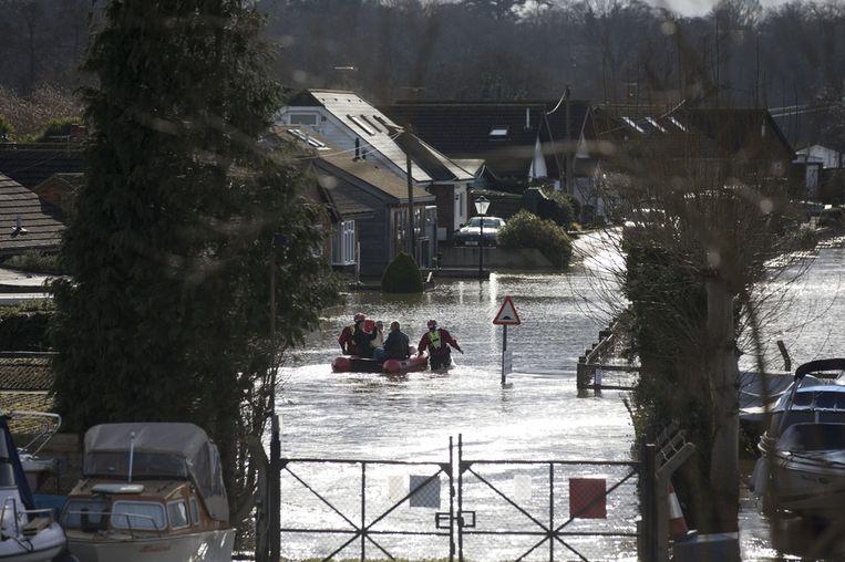 Reddingswerkers in Walton-on-Thames.<br /><br />De Engelse overheid waarschuwt voor ernstig overstromingsgevaar in 14 plaatsen langs de de rivier de Theems. Duizenden huishoudens moeten zich daar op voorbereiden. Sinds december zijn al zo'n 8000 woningen getroffen door het hoge water.<br /><br />Ondanks alle maatregelen is vanmiddag het dorp Datchet ook ondergelopen.<br /><br />Na twee maanden van recordneerslag voorspellen meteorologen nog zeker tot en met donderdag iedere dag regen. Vooral de graafschappen Berkshire en Surrey zullen vermoedelijk met wateroverlast te maken krijgen. <br /><br />De Britten worstelen met het natste weer sinds 1766. Het water in de rivier stond in tientallen jaren niet zo hoog en stijgt nog steeds. Beeld getty