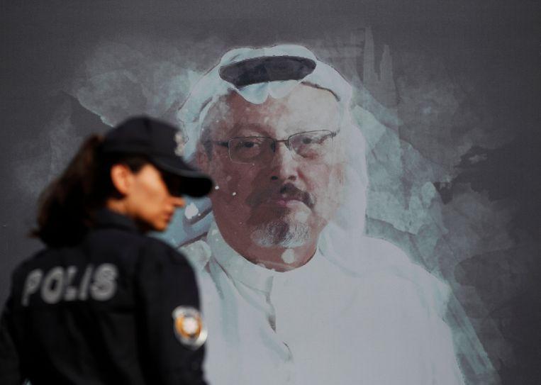 Een Turkse politieagente loopt langs een portret van Jamal Khashoggi op een muur vlakbij het Saoedische consulaat in Istanbul waar de journalist vorig jaar werd vermoord. Beeld AP