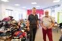 """Cédric Lerusse (burgemeester Rendeux) en Jacques Chapelier (Hotton), bij een berg kleding: """"Kleren hebben we genoeg nu, ook al omdat de meeste mensen hun kleren in een kast op de eerste verdieping hebben hangen. Die zijn niet weggespoeld."""""""