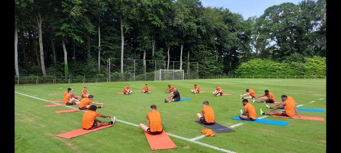 Fysiektrainer Chima Onyeike onderwerpt de selectie aan rek- en strekoefeningen tijdens de eerste training in Oisterwijk.