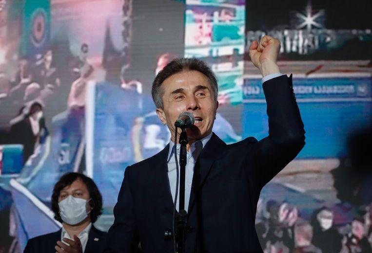 Partijleider Bidzina Ivanisjvili van Georgische Droom neemt een voorschot op de verkiezingswinst tijdens een partijbijeenkomst zaterdagavond in Tbilisi. Beeld EPA