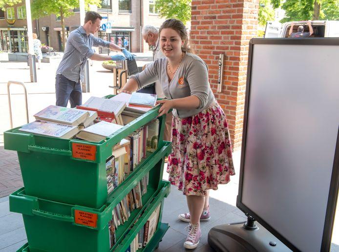 Boeken, boeken en nog eens boeken. De bibliotheek in Ermelo is weer op voor 'afhalers'. Medewerkster Kim Huisman brengt de boeken naar de uitleenbalie.