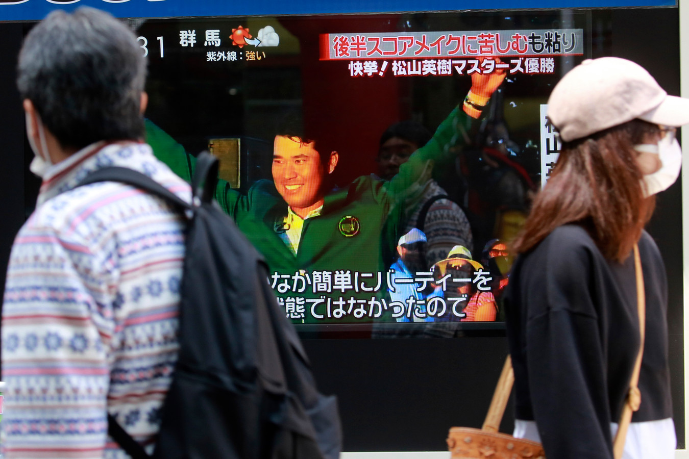 Voorbijgangers in Tokio zien Hideki Matsuyama op tv zijn historische overwinning vieren.