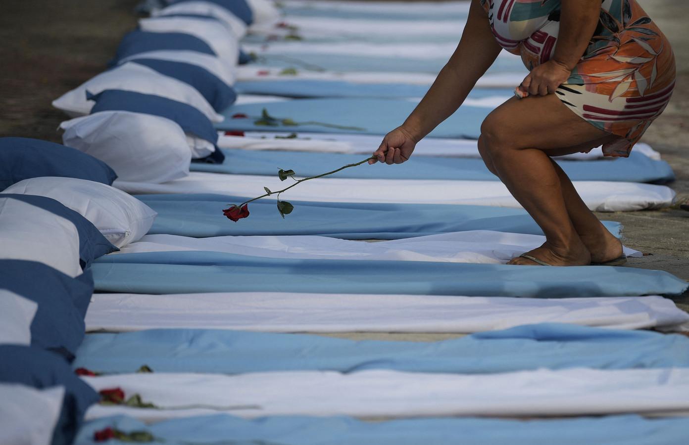 Een vrouw legt een roos op een matras, symbool voor Covid-19-slachtoffers.