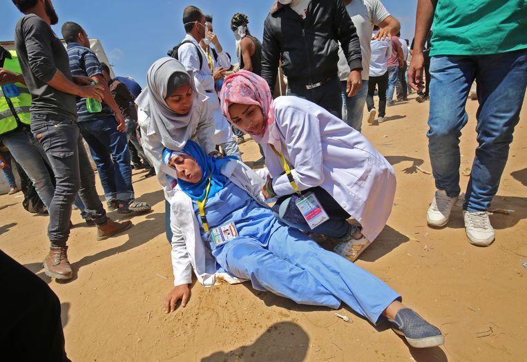 Palestijnse verpleegsters helpen een collega die bij een Israëlische aanval gewond raakte.  Beeld AFP