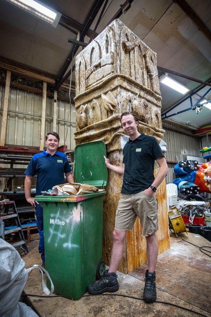 Douwe Emsbroek (links) en Joren Kip van de Blaanke Boeskeulkes bij het afvalmonument, in de vorm van de Plechelmustoren, dat ze voor Het Hulsbeek maken.